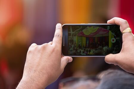 hands holding mobile phones and shoot video on them. bright colored background of Indian concert in blur. the sharpness on the hand with phone
