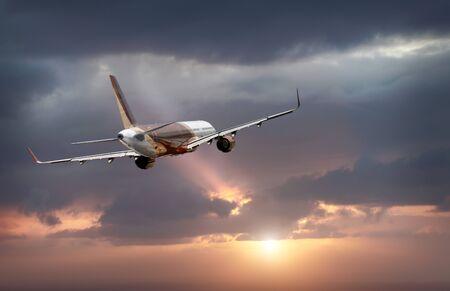 Passagierflugzeug fliegt in den stürmischen dramatischen Himmel. die Sonne scheint hinter den Wolken hervor. das flugzeug fliegt