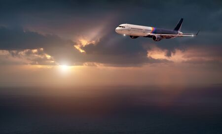 the plane of rainbow color flies in the stormy sky with the evening light of the sun. the plane flies over the dark sea Stock Photo