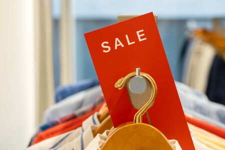goods in stores and a red sign on sales discounts. mocap for text and concept of sales and trade in light industry. sale in the clothing store Standard-Bild