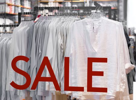 goods in stores and a red sign on sales discounts. mocap for text and concept of sales and trade in light industry. the sale of advertising in a glass case