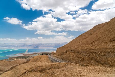 landscape in the mountain desert near the dead sea in Israel. road with a car and the sea seen in the distance