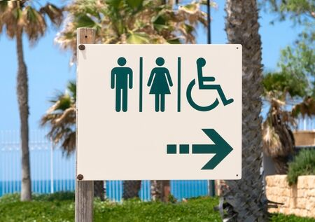 sign in the toilet against the palm trees in the Israeli Park