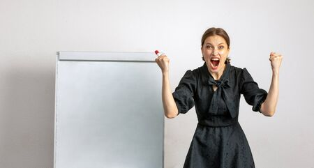the emotions of an angry female teacher standing near a blackboard and a wall Stock Photo