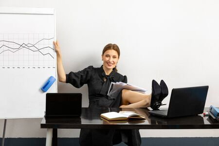 successful and joyful girl working in the office. the girl sitting at the table her feet on the table her hand she held a Board which is drawn work schedule. on the table two laptop and documents