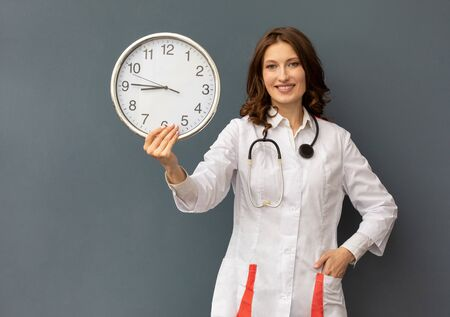 a woman doctor with a stethoscope around her neck and a large wall clock in her hands. the concept of time that cures Stock fotó