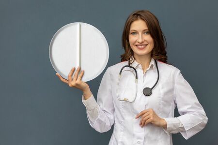 a woman doctor with a large pill in her hands. doctor shows a large tablet. doctor has a stethoscope on his shoulders