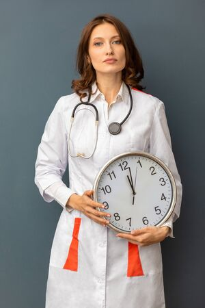 a woman doctor with a stethoscope around her neck and a large wall clock in her hands. doctor smiles . the concept of time that cures. vertical frame Stock fotó