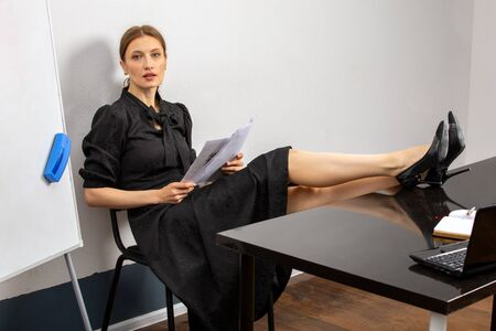 a female teacher sits at her Desk in the classroom and has her feet on the table