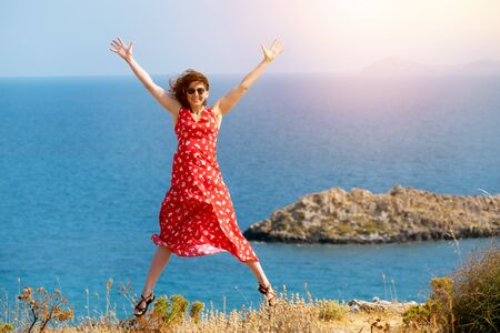 the girl in the red dress jumps with joy. She is on vacation by the sea. behind her the sea horizon and a small island on the background Stock fotó
