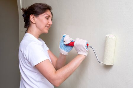 a woman makes repairs in the apartment. She paints the walls with a paint roller. shes wearing a white t-shirt.