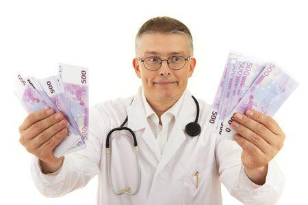 ein Arzt im Kittel hält viel Geld Euro und freut sich