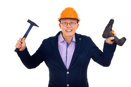 male builder in a jacket and orange helmet on an isolated background. in his hands he holds a drill and a hammer Standard-Bild