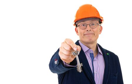 a man in an orange construction helmet offers two keys to the constructed apartment. isolated background Фото со стока