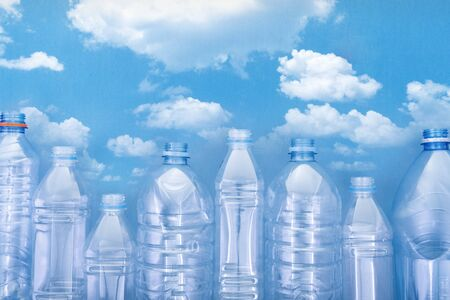plastic bottles on blue cardboard with a picture of a blue sky with white clouds. the concept of the city of bottles Stock fotó