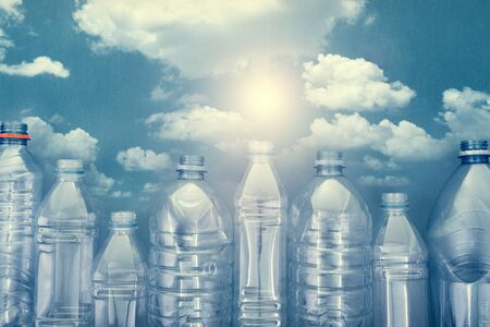 plastic bottles on blue cardboard with a picture of a blue sky with white clouds and a bright sun. the concept of the city of bottles