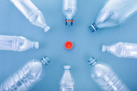 plastic bottles on a blue cardboard background. concept ecology and science. in the shape of a circle or sun