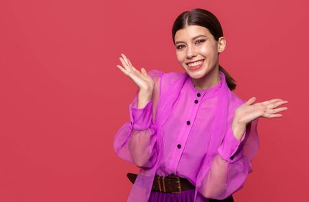 girl actress posing with positive emotion. in the Studio on a red background