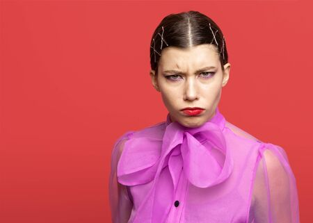 girl frowns and expresses discontent. girl posing on red background
