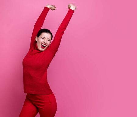 girl in red sweater posing on pink studio background. positive emotions. artistic girl. free space for copy paste Archivio Fotografico - 132305299