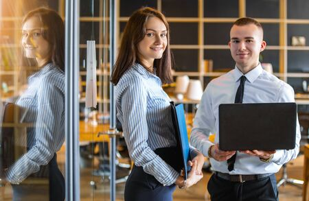 a young woman holding documents and a young man with a laptop in his hands working in the office of the company. portrait of young professionals Archivio Fotografico