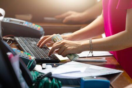 La femme tient cent dollars et tape quelque chose sur le clavier