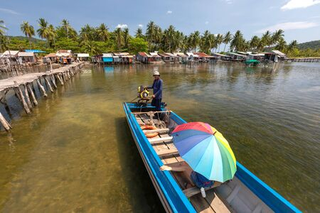 Vietnam Phu Quoc island 2 April 2019. Vietnamese boat driver with a motor carries a tourist with a bright umbrella. in the background behind them is a fishing village