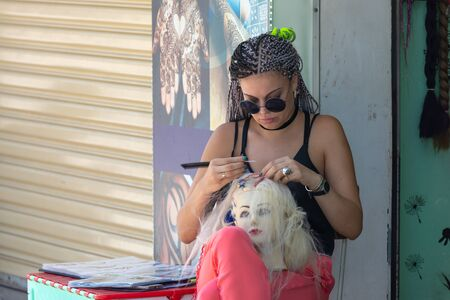 Vietnam, Nha Trang city, March 25, 2019. a woman braids on the head of a mannequin on the street of Nha Trang