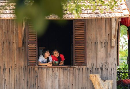 Vietnam Phu Quoc island 2 April 2019. two waitress girls look cautiously out the open window of the cafe from the burning in the air Editoriali