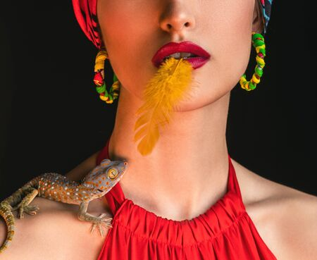 a fragment of a portrait of a model in a red dress and with an orange bird feather on her tongue. a colored lizard sits on the womans shoulder and looks up at the models face