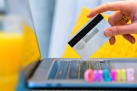 mano femenina con tarjeta de crédito y pago en línea usando laptop. en la computadora portátil en el desenfoque hay letras de colores Foto de archivo
