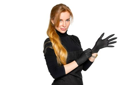 a blonde woman in black medical latex gloves poses on an isolated white background. a woman in dark clothing of a beauty salon employee. the concept of hygiene and protection