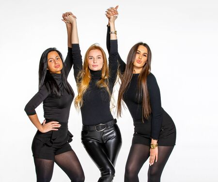 three young female friends pose together in the Studio. women in their success. concept of friendship and communication