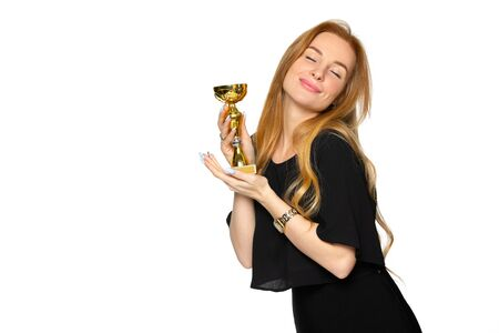 a young blonde woman with a souvenir award in her hands. winner of the contest. the concept of victory and recognition.
