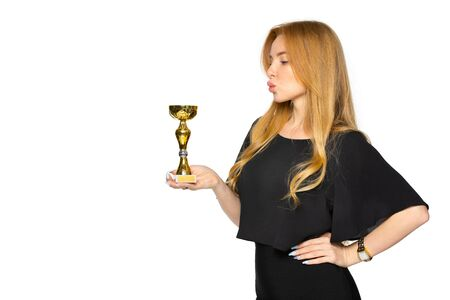 a young blonde woman with a souvenir award in her hands. winner of the contest. the concept of victory and recognition. Archivio Fotografico - 142859269