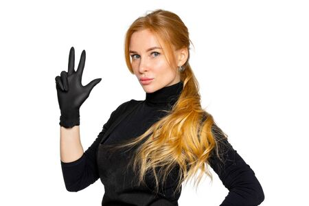 a blonde woman in black medical latex gloves poses on an isolated white background. a woman in dark clothing of a beauty salon employee. the concept of hygiene and protection Archivio Fotografico - 142847662