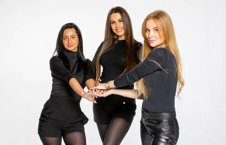 three young female friends pose together in the Studio. women hold hands. women employees of a beauty salon