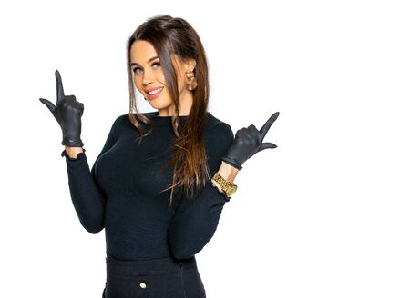 a woman in black medical latex gloves poses on an isolated white background. a woman in dark clothing of a beauty salon employee. the concept of hygiene and protection Archivio Fotografico