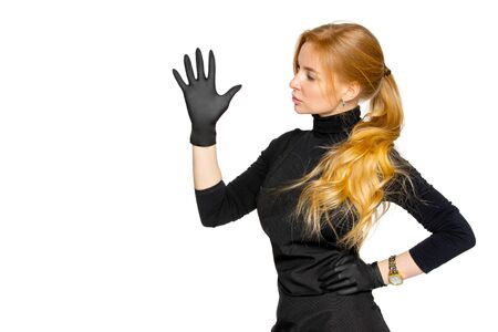 a blonde woman in black medical latex gloves poses on an isolated white background. a woman in dark clothing of a beauty salon employee. the concept of hygiene and protection Archivio Fotografico - 142847753