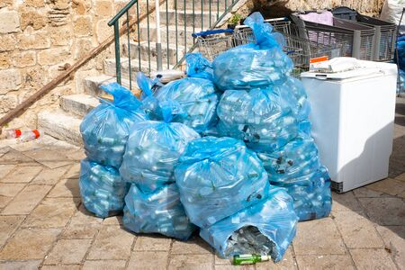 garbage in plastic blue bags on the street of the Eastern city. in blue bags plastic bottles Archivio Fotografico - 142076864