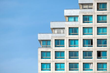 a fragment of a modern building against the blue daytime sky. the building is built on the principle of stairs. Archivio Fotografico