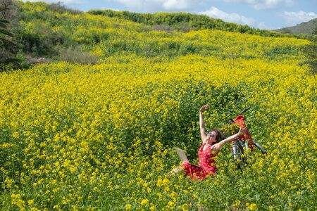 a freelancer girl works behind a laptop in a spring flower and sunny field. the girl came to the field on a Bicycle and he is standing next to her Archivio Fotografico - 142260494