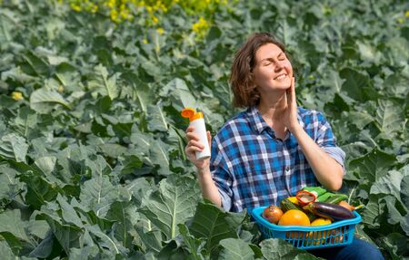 woman working on an agricultural field during a sunny day and protecting her skin from the sun with sunscreen. woman holds a basket with collected vegetables on her lap