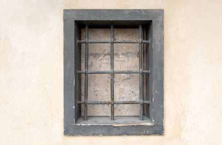 window with bars in the old city. there is one window on the wall which is closed and with a strong grating. prison in the city Archivio Fotografico - 144047630