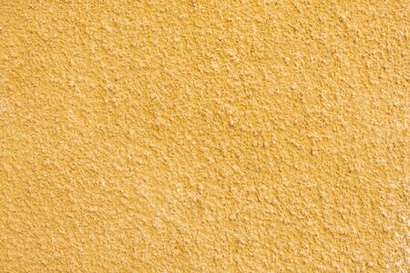 the texture of the wall is made of old yellow plaster Archivio Fotografico