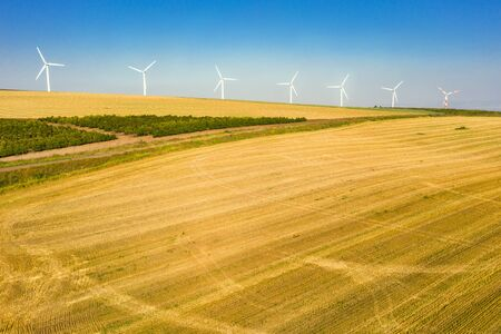 White wind power generators rotate in an agricultural field in Israel. yellow field and blue sky