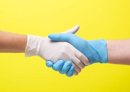 yellow background and hands in medical gloves. woman and a man. medical collaboration and doctors hold hands to each other Archivio Fotografico