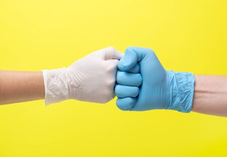 yellow background and hands in medical gloves. hands in latex medical gloves punch each other. one hand in a blue glove and the second hand in a white glove. woman and a man Archivio Fotografico - 147560058