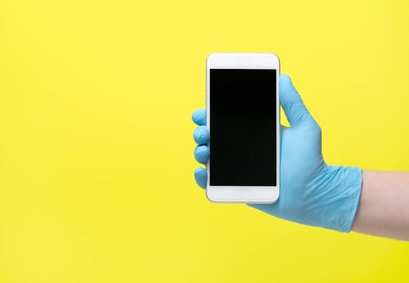 yellow background and hand in medical glove. Male hand in latex medical blue glove shows mobile phone screen Archivio Fotografico - 147560061