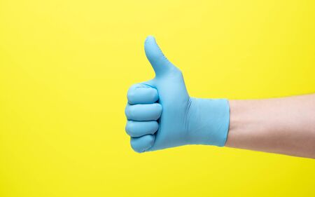 yellow background and hand in medical gloves.male hand in latex medical blue glove shows good luck gesture 免版税图像